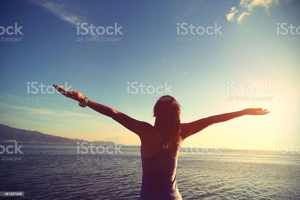 cheering young woman open arms at sunrise seaside stock photo