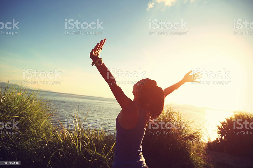 cheering young woman runner open arms at sunrise seaside stock photo