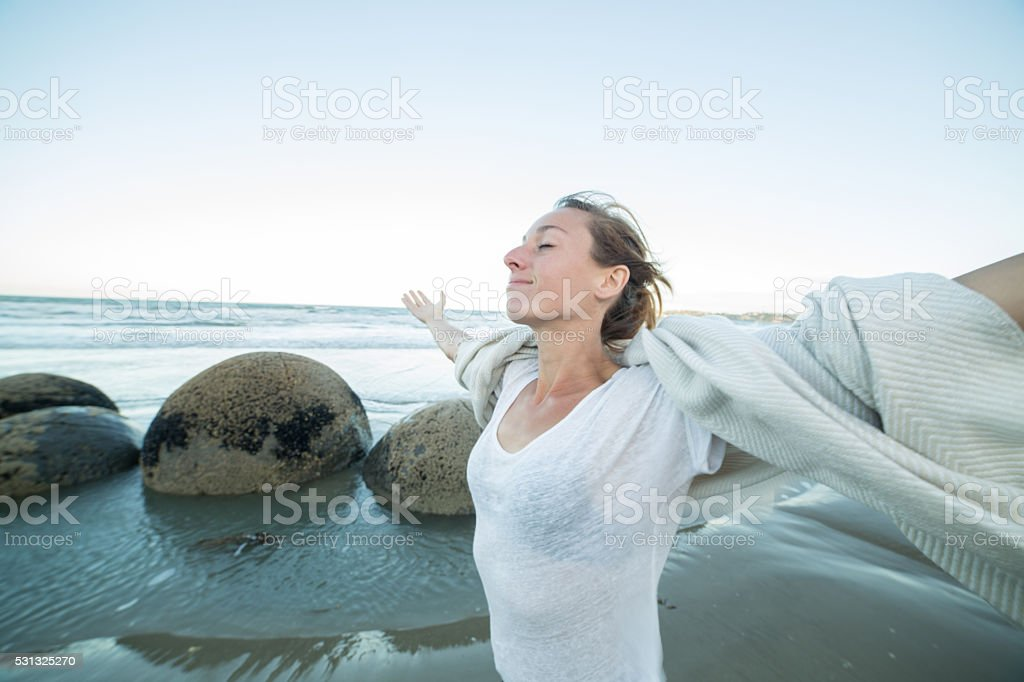 Cheering young woman stands by the Moeraki boulders, arms outstretched stock photo