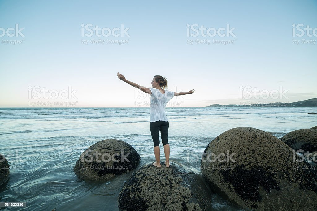 Cheering young woman stands on a boulder at Moeraki boulders stock photo