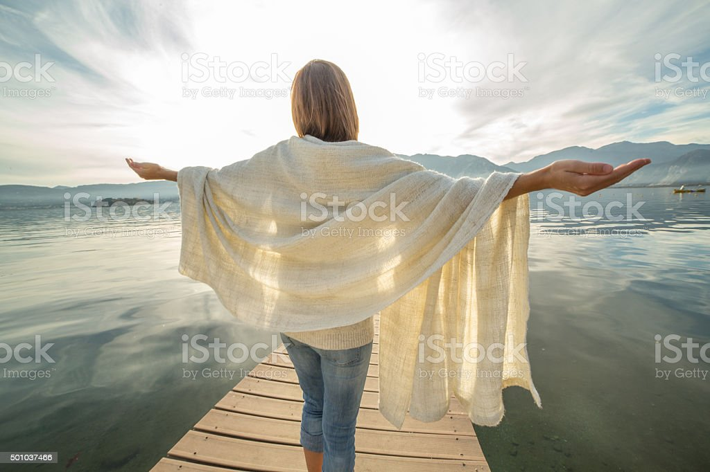 Cheering young woman stands on pier arms outstretched stock photo