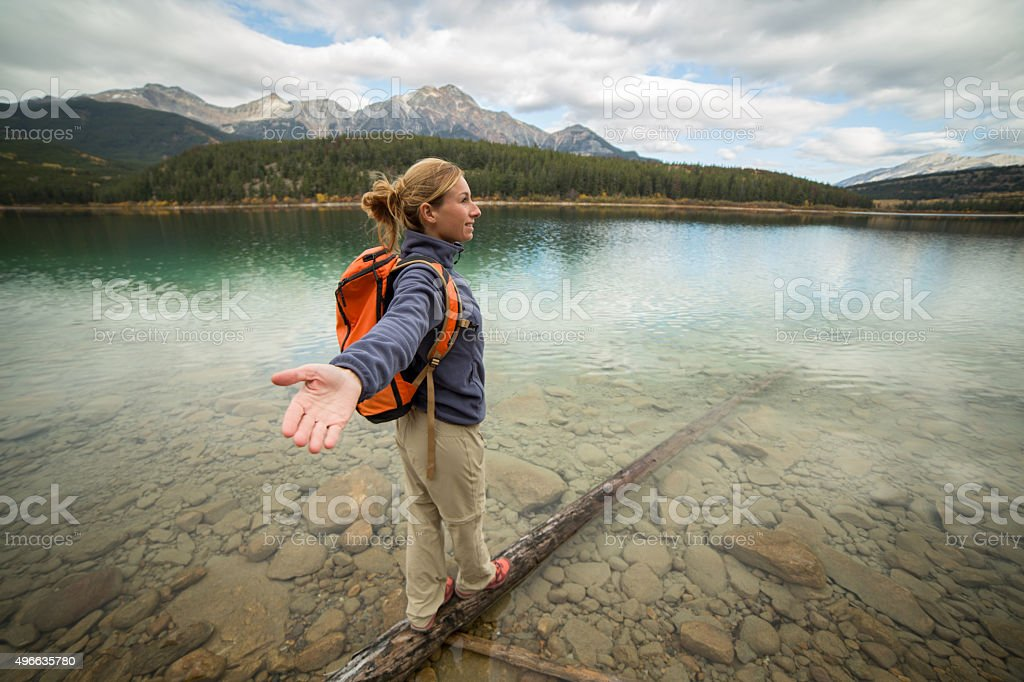 Cheering young woman walking on log arms outstretched stock photo