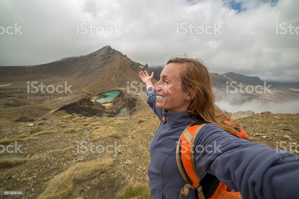 Cheeringl young woman arms outstretched on Tongariro Alpine Crossing stock photo