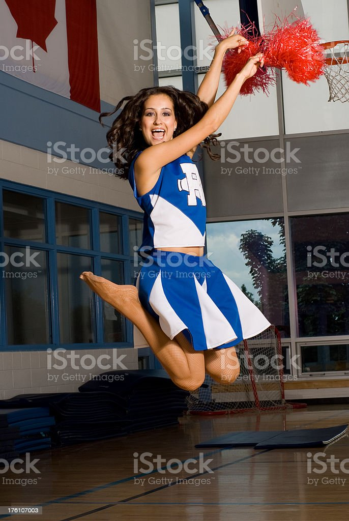 Cheerleader Jumping in a School Gym stock photo