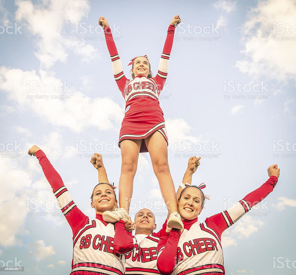 Cheerleader team with a male member posing stock photo