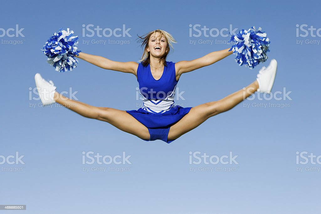 Cheerleader With Pompoms Doing Splits Against Sky stock photo