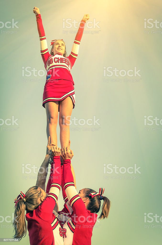 Cheerleaders in action on a vintage filtered look stock photo