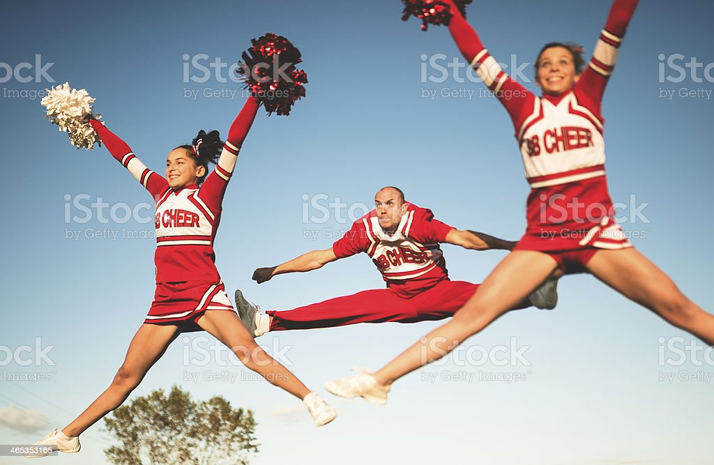 cheerleaders jumping team with pon-pon stock photo