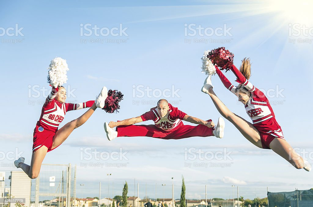 Cheerleaders team performing a Jump with male Coach stock photo