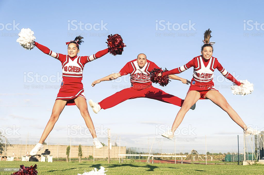 Cheerleaders team with male Coach performing a synchronized jump stock photo