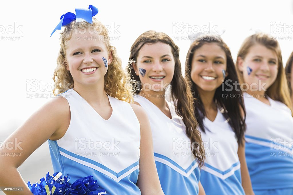 Cheerleading squad practicing routine on high school field royalty-free stock photo