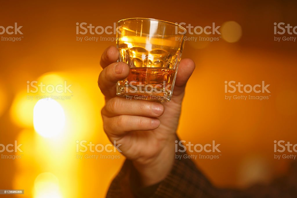 Cheers   Old fashioned  Men's hand holding a glass of whiskey stock photo