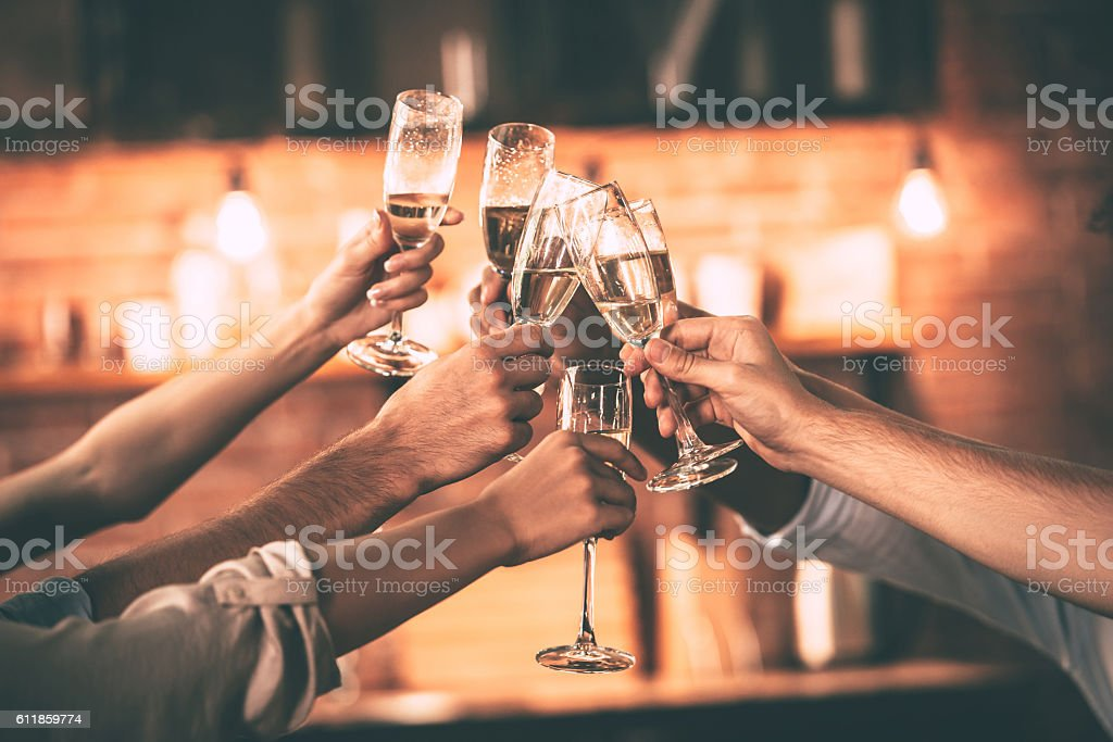 Group of people cheering with champagne flutes with home interior in...