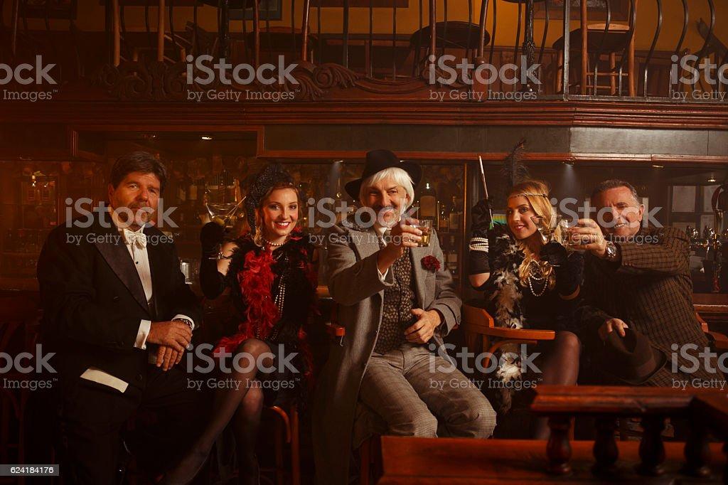Cheers Retro pub celebration  Senior men and young woman drinking stock photo