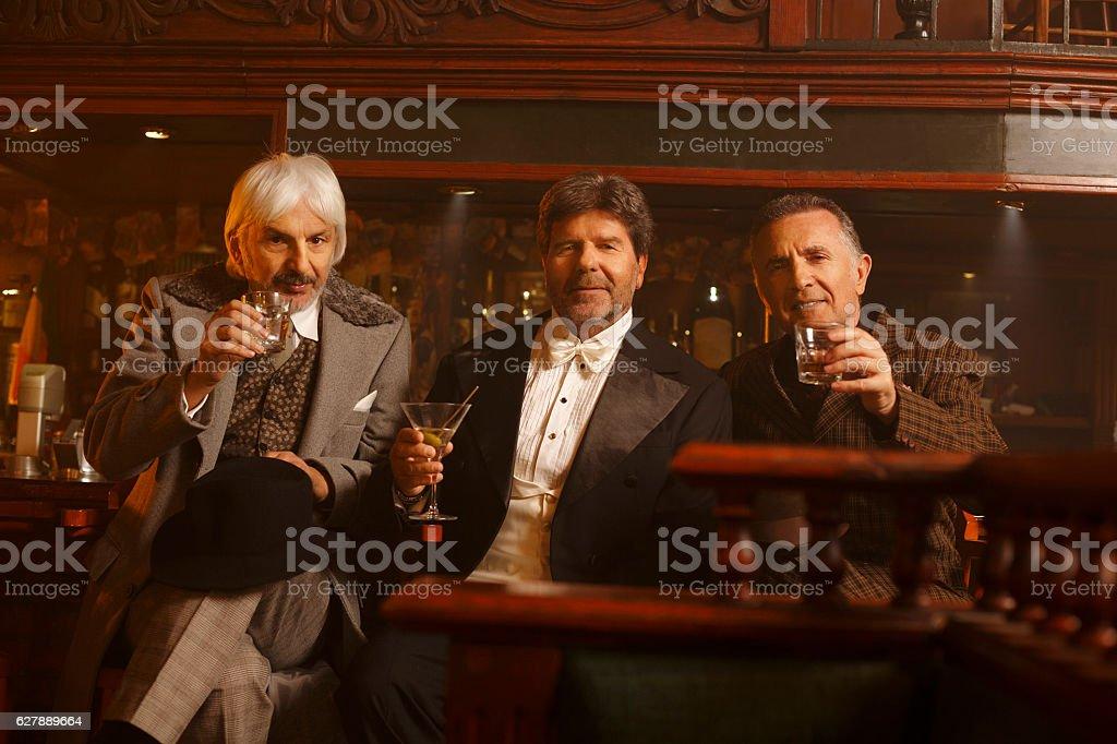 Cheers Retro pub celebration  Senior men  drinking whiskey and martini stock photo