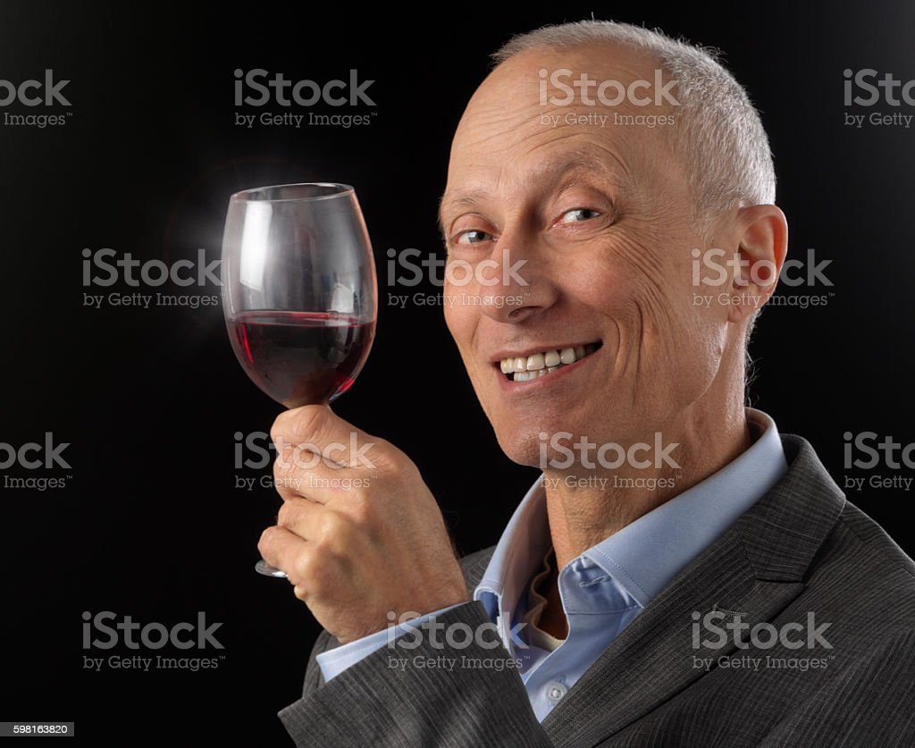 Cheers! Smiling mature man holds up glass of red wine stock photo