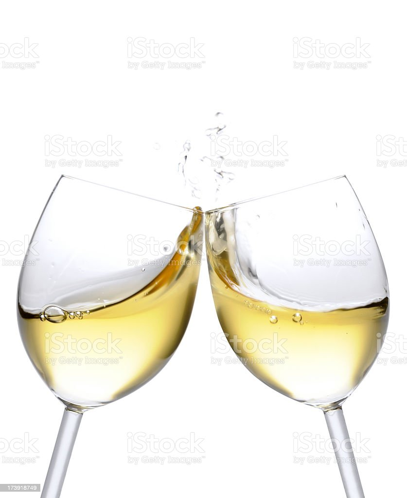 Cheers! Two white wine glasses with splash, isolated on white stock photo