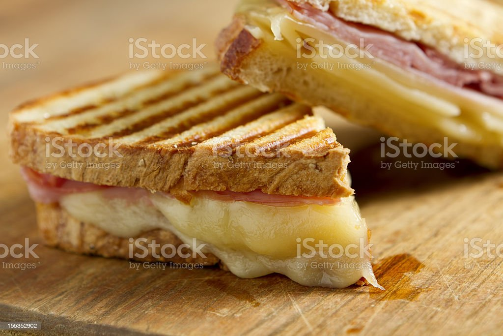 Cheese and ham panini sandwiches on a wooden board stock photo