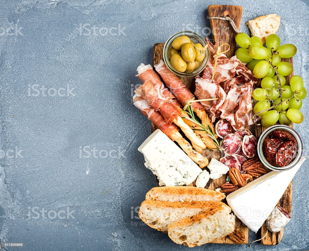 Cheese and meat appetizer selection. Prosciutto di Parma, salami, bread stock photo
