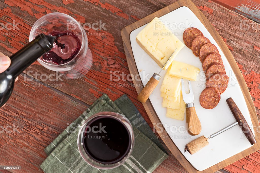 Cheese and Sausage on Board with Glasses of Wine stock photo