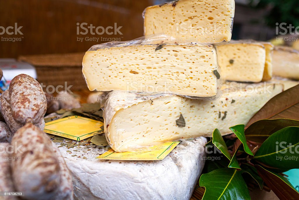Cheese and sausages exposure in a market stall. Color image stock photo