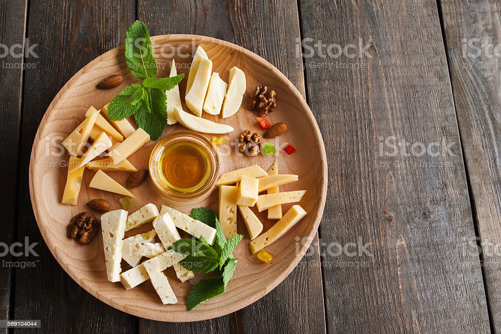 Cheese assortment plate on wood, free space stock photo