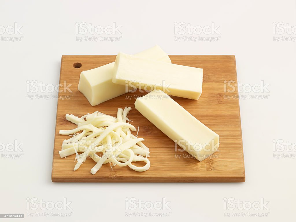 Cheese blocks and shaved cheese on chopping board stock photo