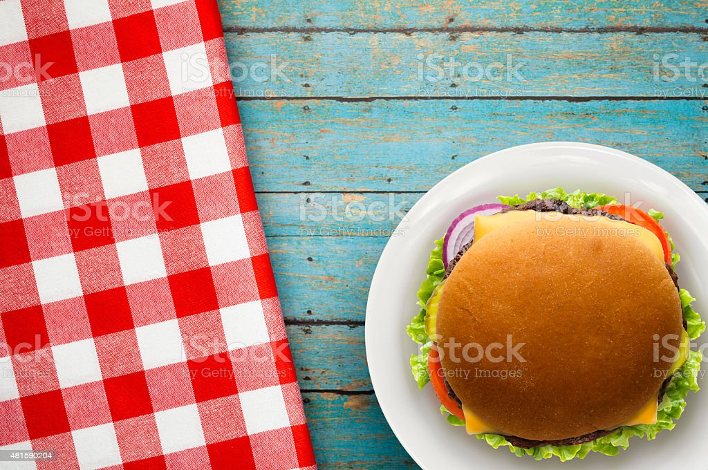 Cheese Burger on Blue Picnic Table with Red Checked Napkin stock photo
