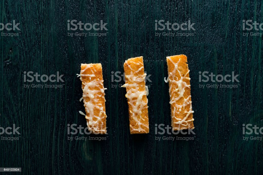cheese croutons on the dark deep blue wooden table stock photo