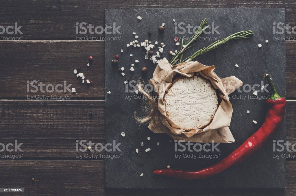 Cheese delikatessen with chili on black stone, brie camembert stock photo