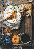 Cheese, fruit and wine set over wooden background, copy space