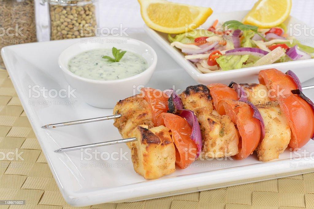 Cheese kebabs on metal skewers on white plate royalty-free stock photo