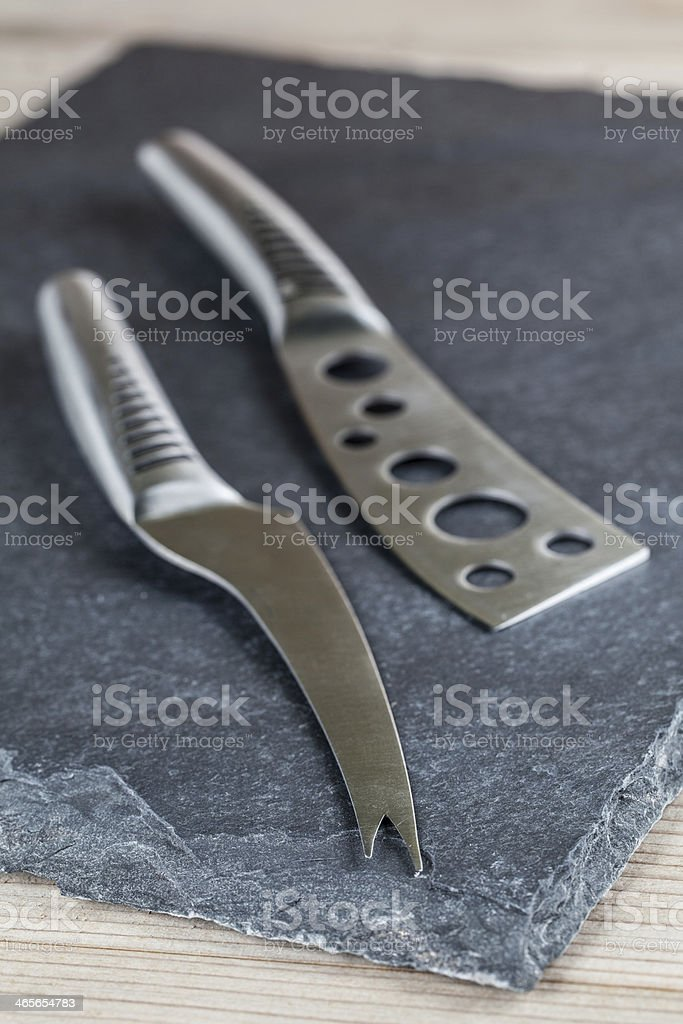 Cheese knives on slate board royalty-free stock photo
