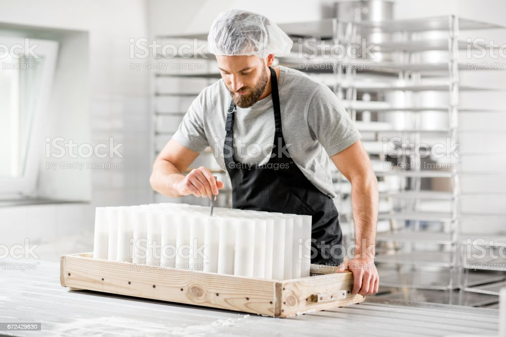 Cheese maker at the manufacturing stock photo