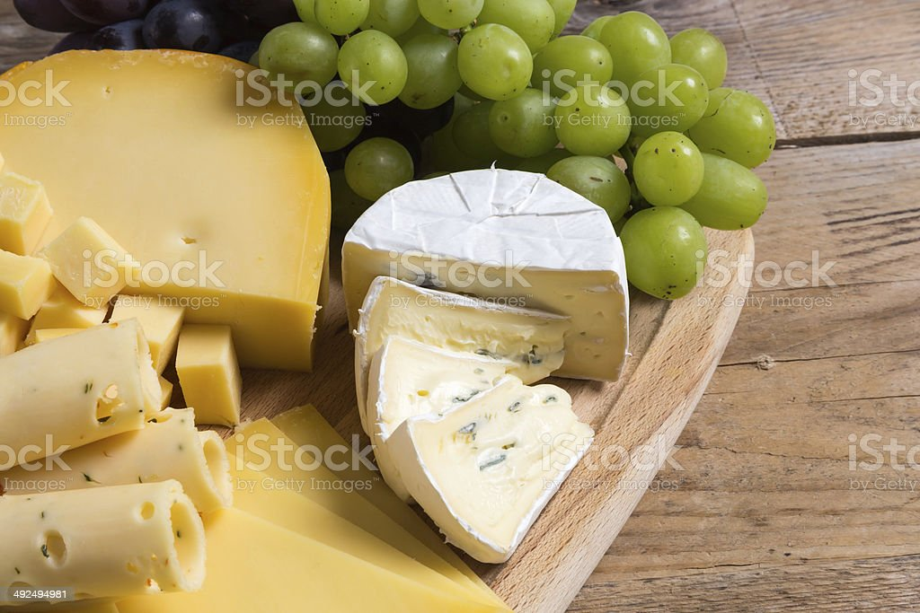 Cheese plate variation on a wooden table stock photo