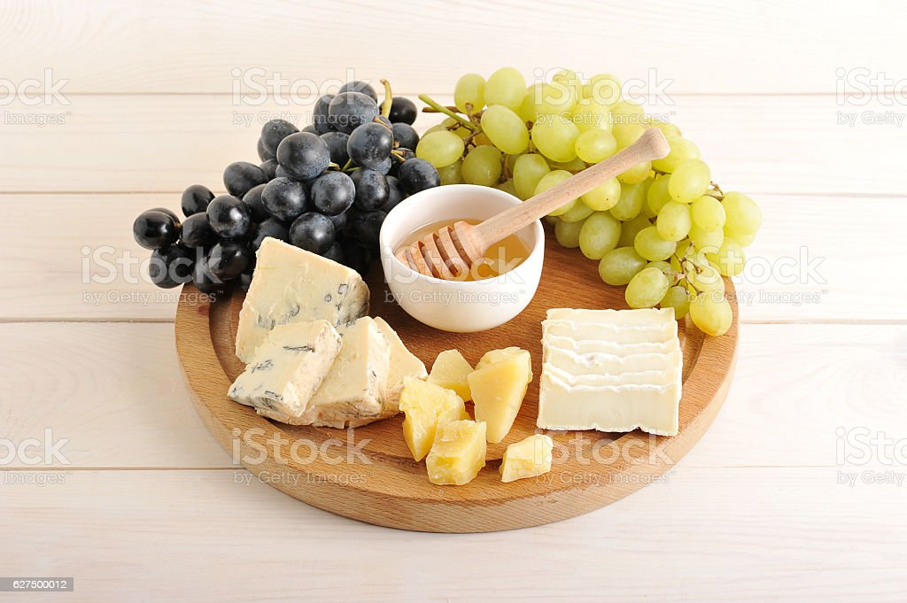 cheese plate - various types of cheese, grapes green and stock photo