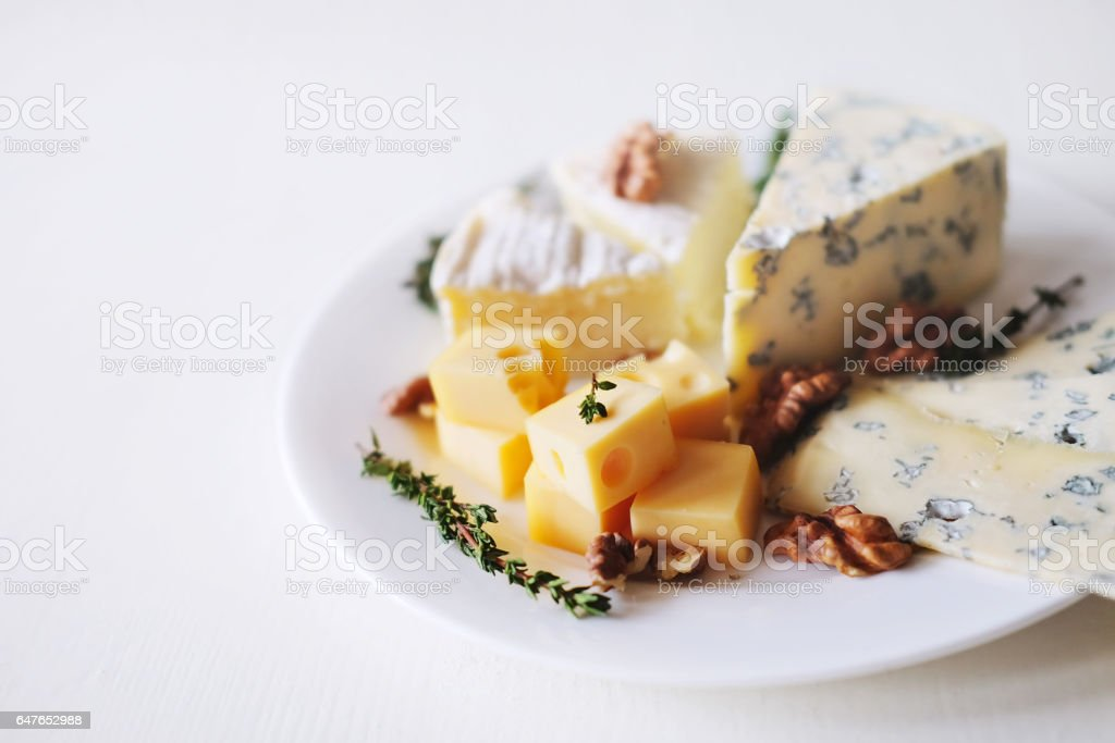 Cheese plate with different kinds of cheese with thyme herbs and walnuts stock photo