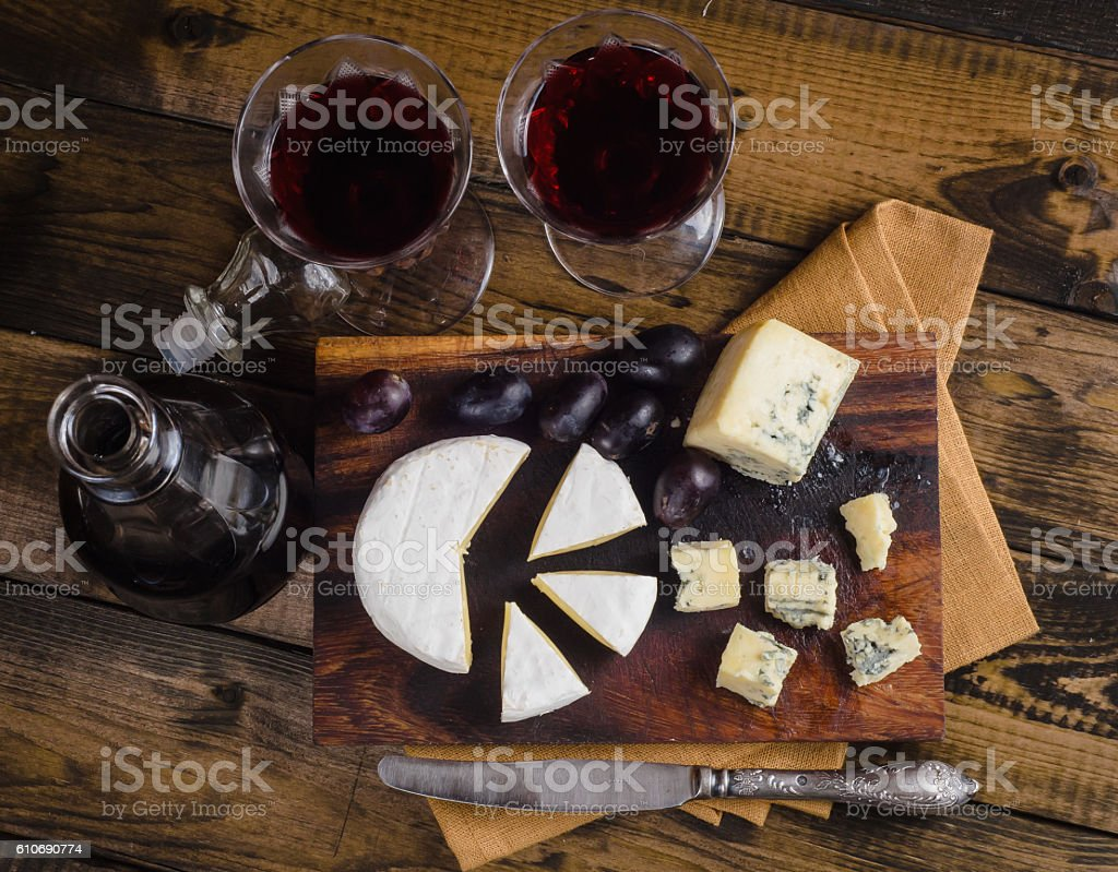 Cheese plate with grape and wine on wood stock photo
