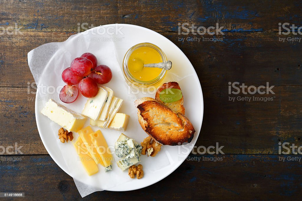 Cheese plate with honey, grapes, bread and walnuts stock photo