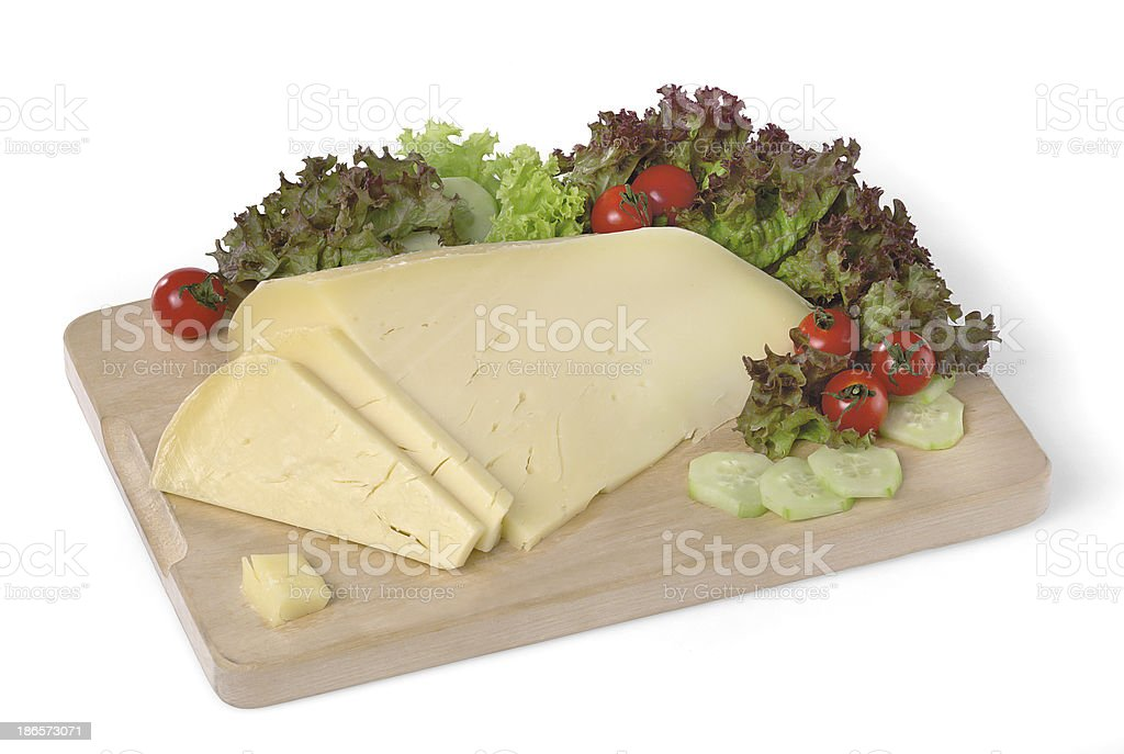 Cheese, salad, tomatoes and cucumber slices over chopping board, still-life stock photo