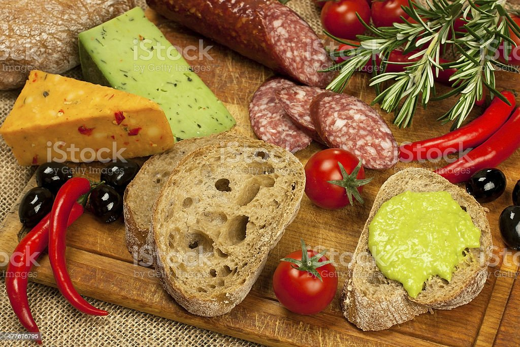 Cheese, salami and bread  on a board royalty-free stock photo