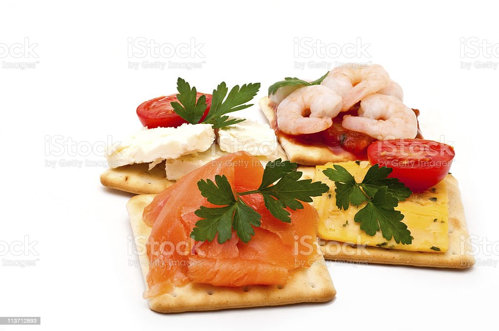 Cheese, salmon, prawns on crackers stock photo