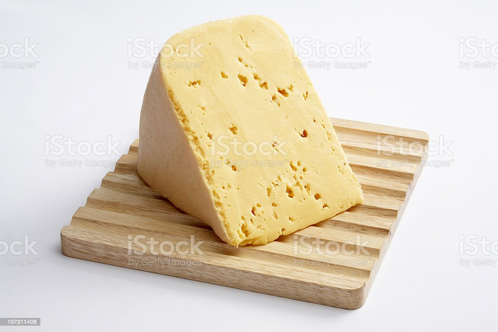 Cheese slice on wood chopper board royalty-free stock photo