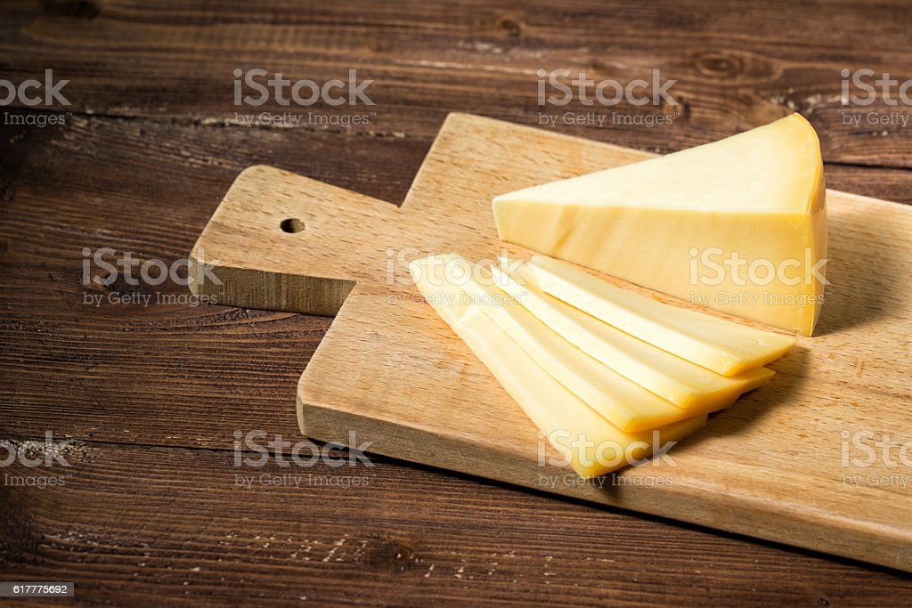 Cheese sliced on a wooden cutting board stock photo