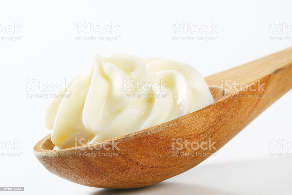 Cheese spread on wooden spoon stock photo