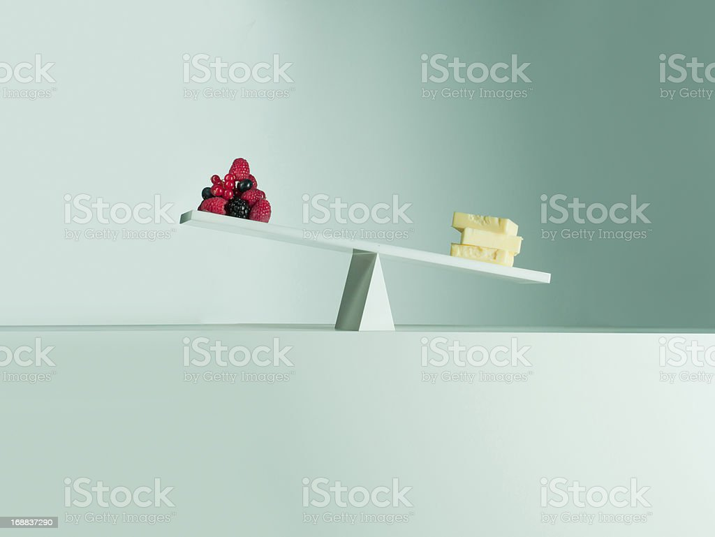 Cheese tipping seesaw with berries on opposite end royalty-free stock photo