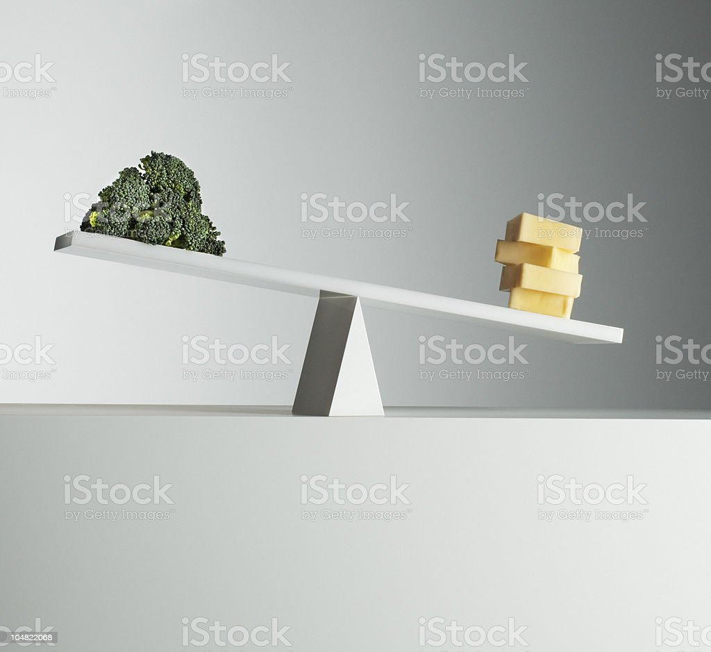 Cheese tipping seesaw with broccoli on opposite end stock photo