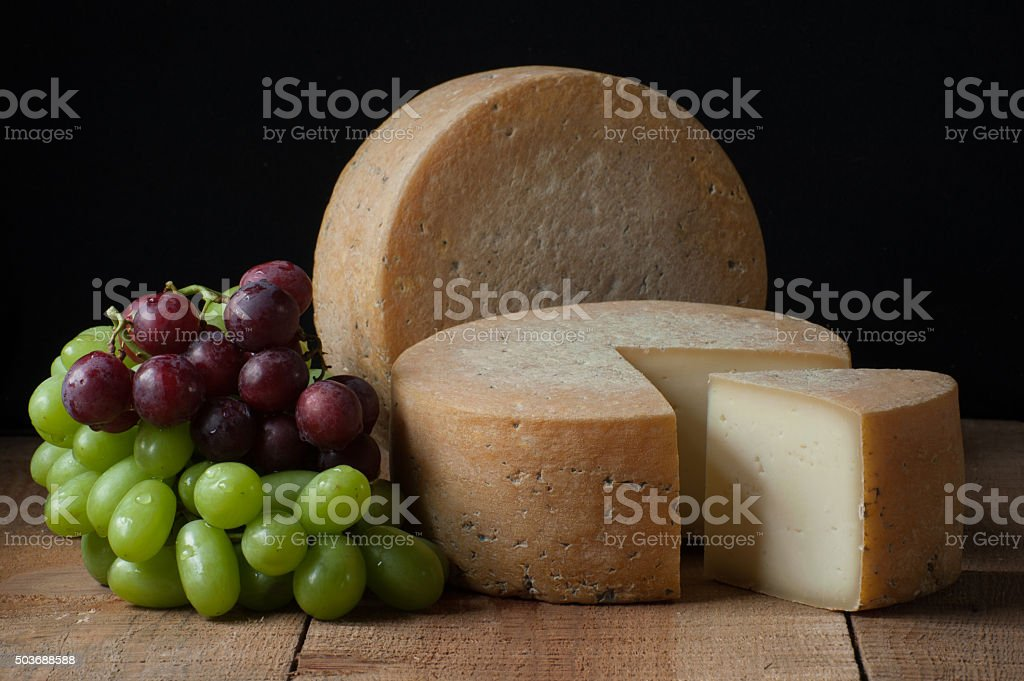 Cheese wheel with grapes studio stock photo