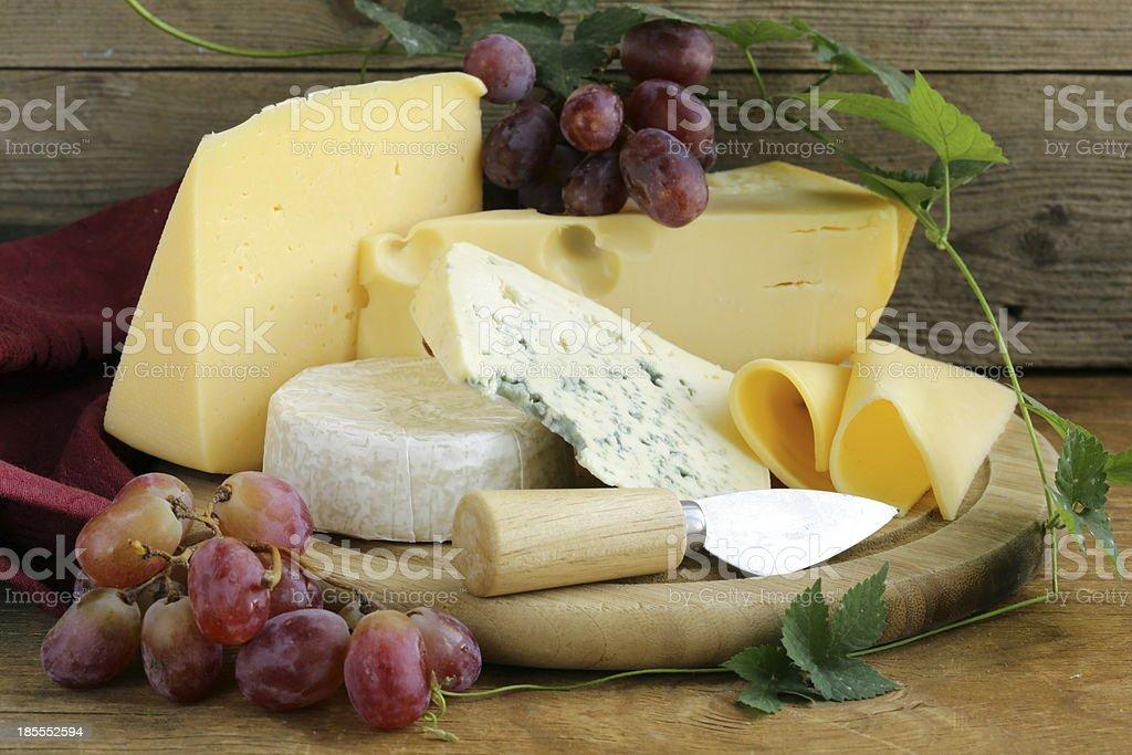 cheeseboard (Maasdam, Roquefort, Camembert) and grapes stock photo