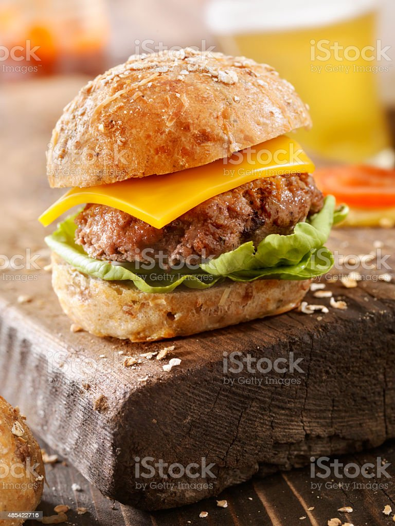 CheeseBurger and a Beer on a Rustic Wood Cutting Board stock photo